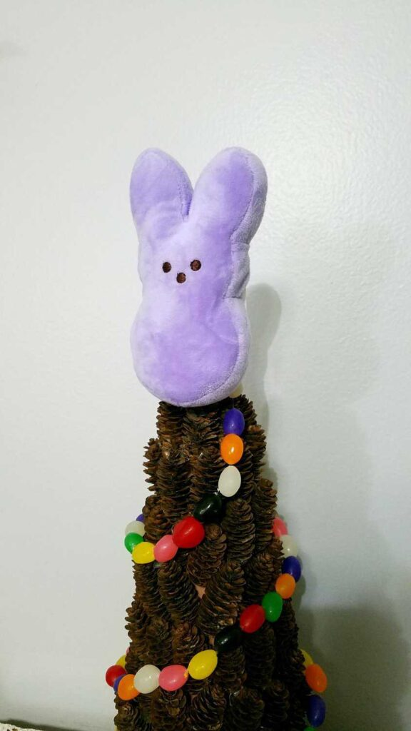 closeup of plush bunny Peep on a pine cone tree draped with a jelly bean garland