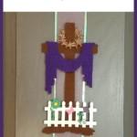 Easter Felt Cross with purple robe draped, on a kitchen cupboard door