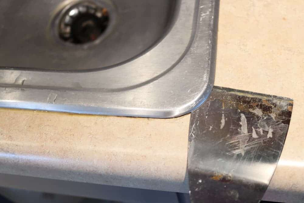 using a putty spatula to lift old sink off of kitchen counter