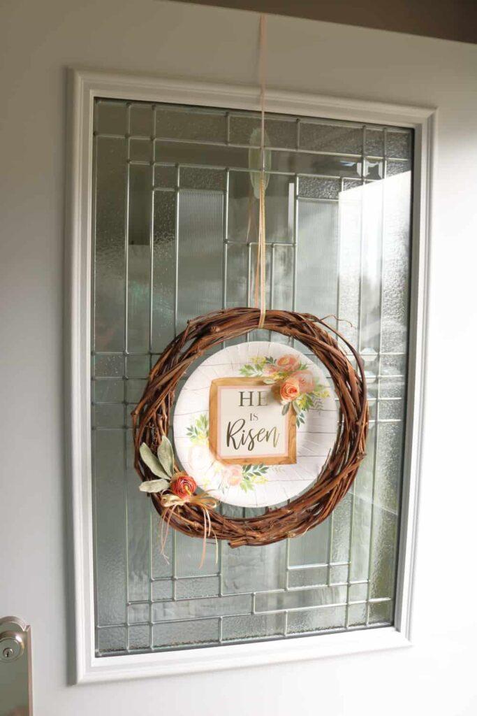 He is Risen Easter wreath hanging from door