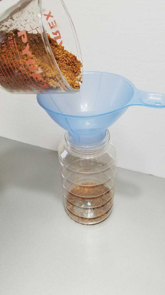 bacon bits being poured through a wide mouth blue funnel into a clear container