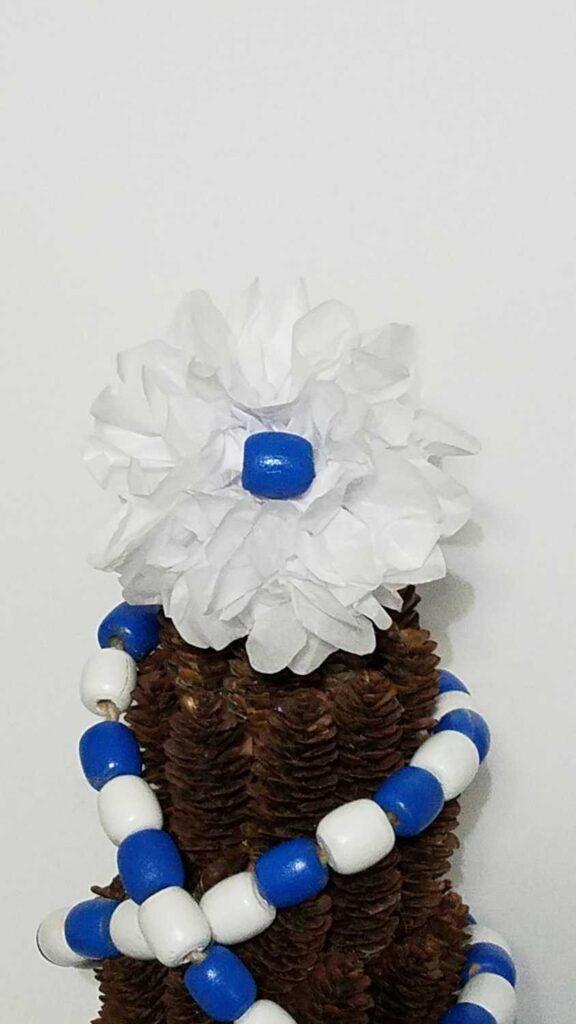 white tissue paper flower with blue bead center
