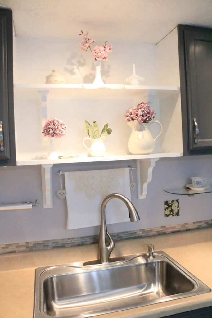 pink flowers on shelves with faucet