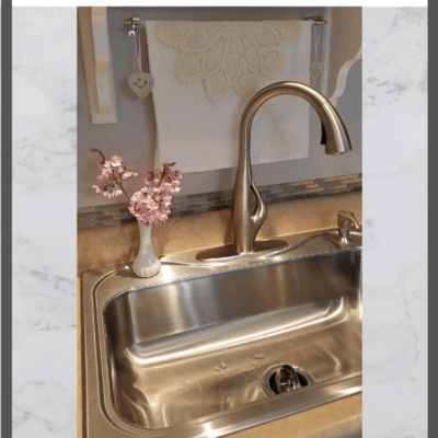 pull down kitchen faucet with pink flowers in a vase beside it