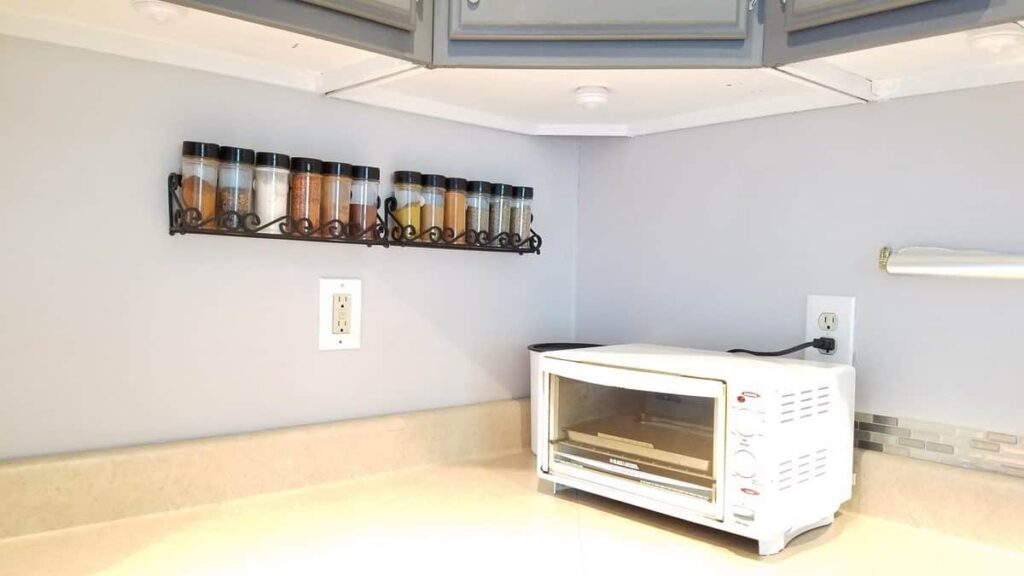 painted white underside of upper kitchen cabinets, also spice bottles on wall, and toaster on counter