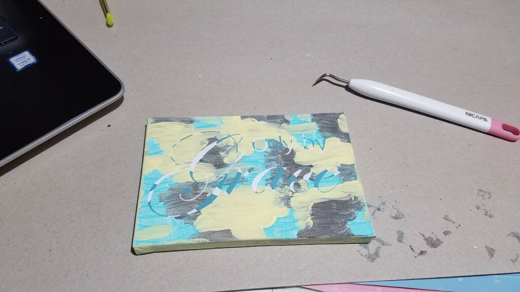 adhering the stencil to the painted canvas
