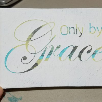 reverse stencil painting that says Only by Grace