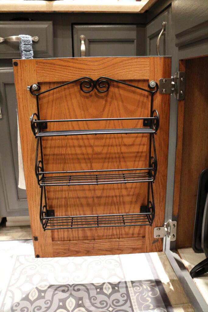 three shelf metal spice rack on inside of kitchen cabinet door