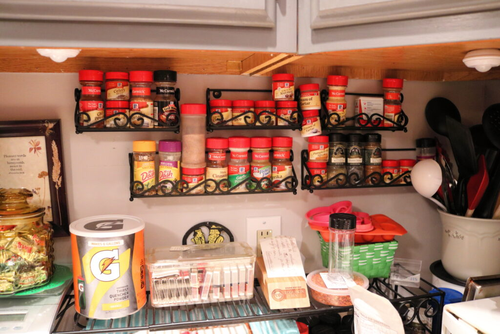 messy spice racks on kitchen wall