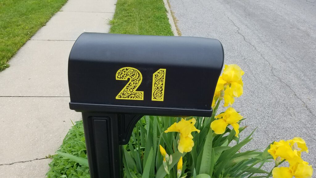 black mailbox with yellow numbers 21 on side