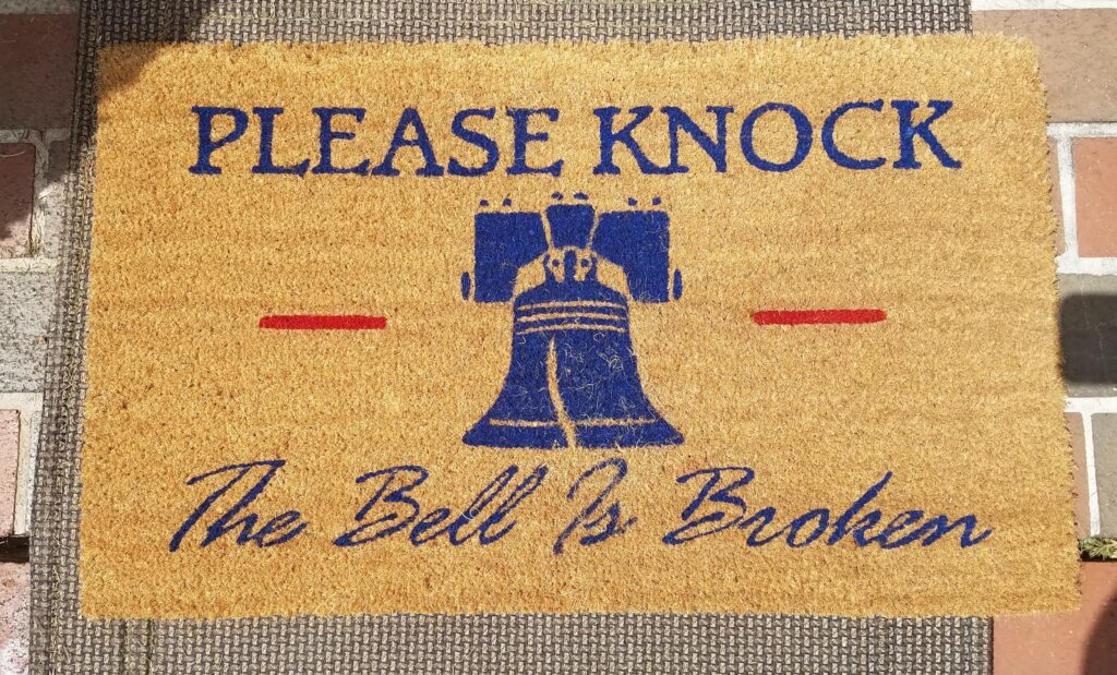 """foot doormat that has a picture of the Liberty Bell and the words """"Please Knock The Bell is Broken"""""""