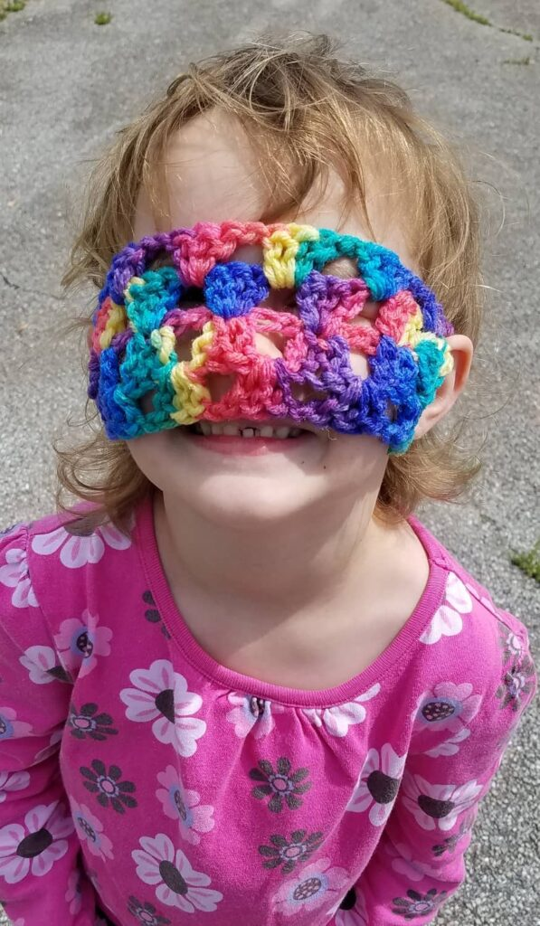 colorful towel holder worn over eyes as a sleep mask