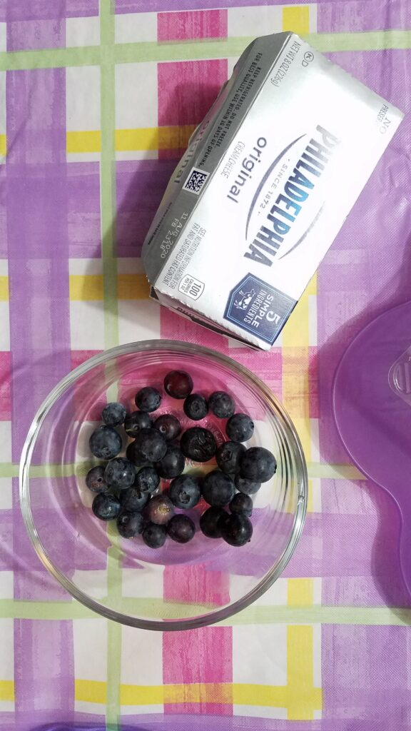 a box of Philadelphia Cream Cheese with some fresh blueberries in a clear glass bowl