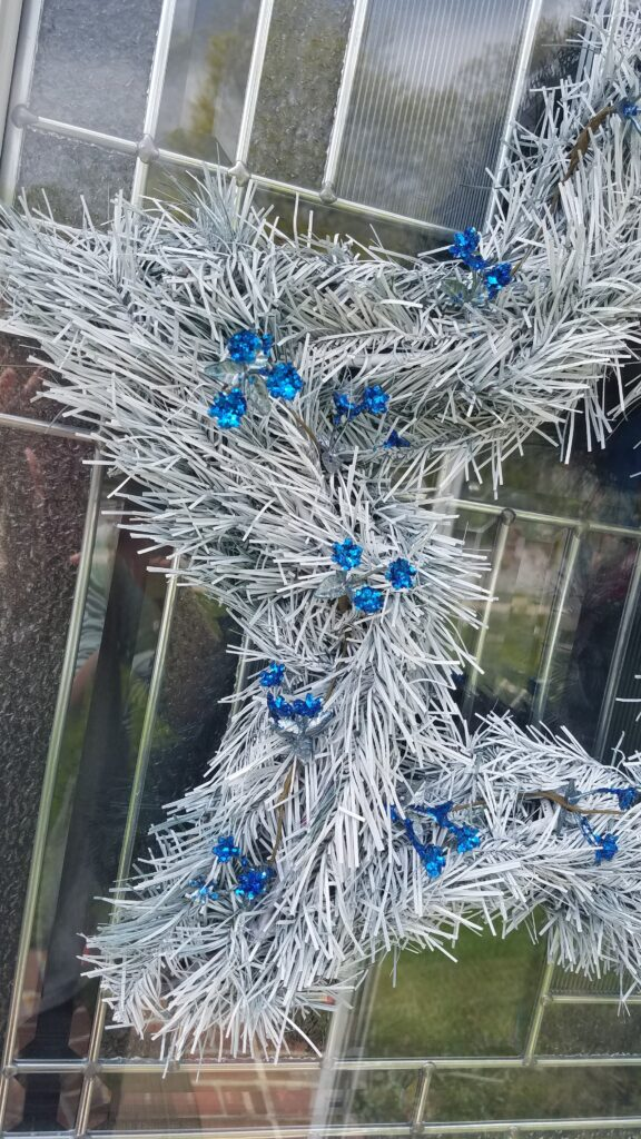 closeup of sparkly blue flower accents on star shaped wreath