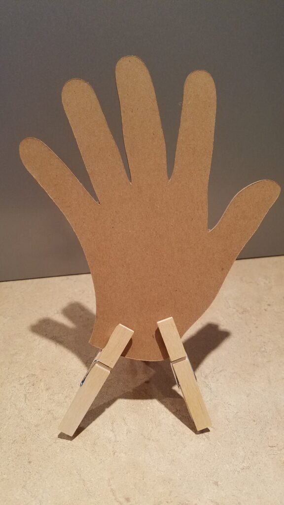 cut out hand propped up with two clothespins