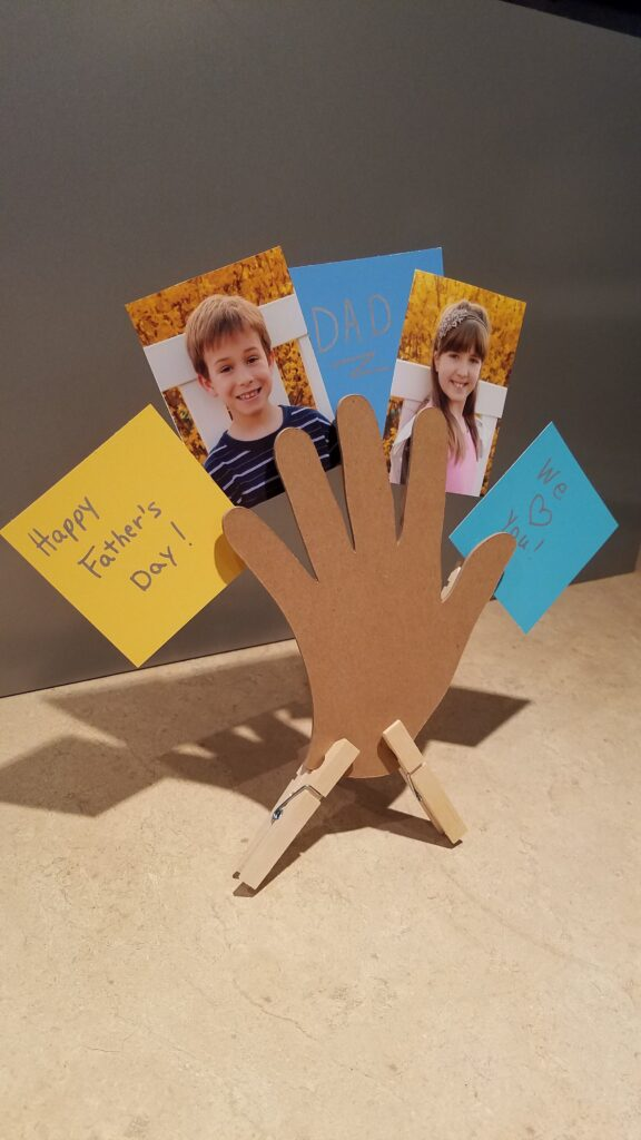 vertical picture of cut out hand standing on countertop holding children's pictures and notes to dad