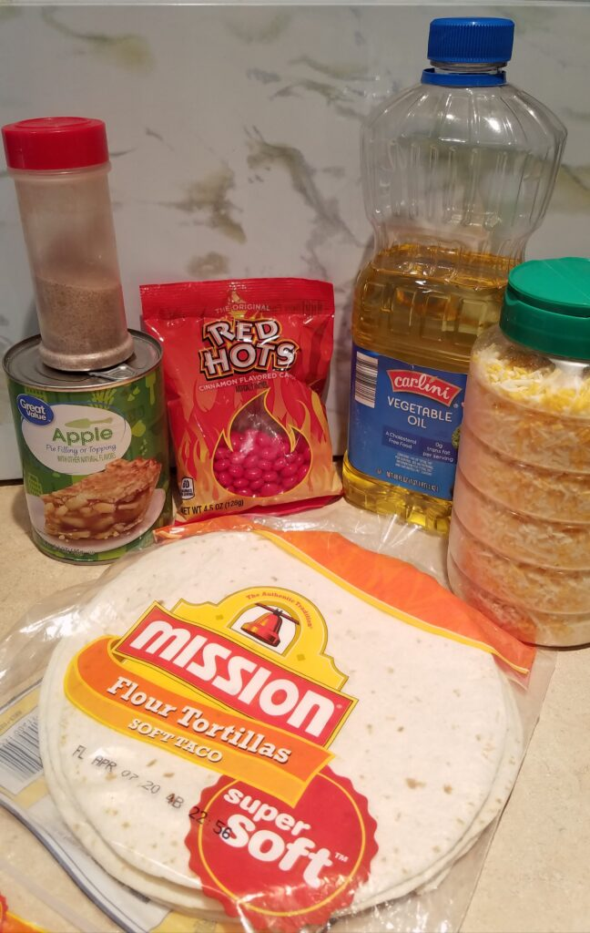 ingredients needed to make apple grande including flour tortillas, vegetable oil, shredded cheese, red hot candies, cinnamon sugar, and a can of apple pie filling