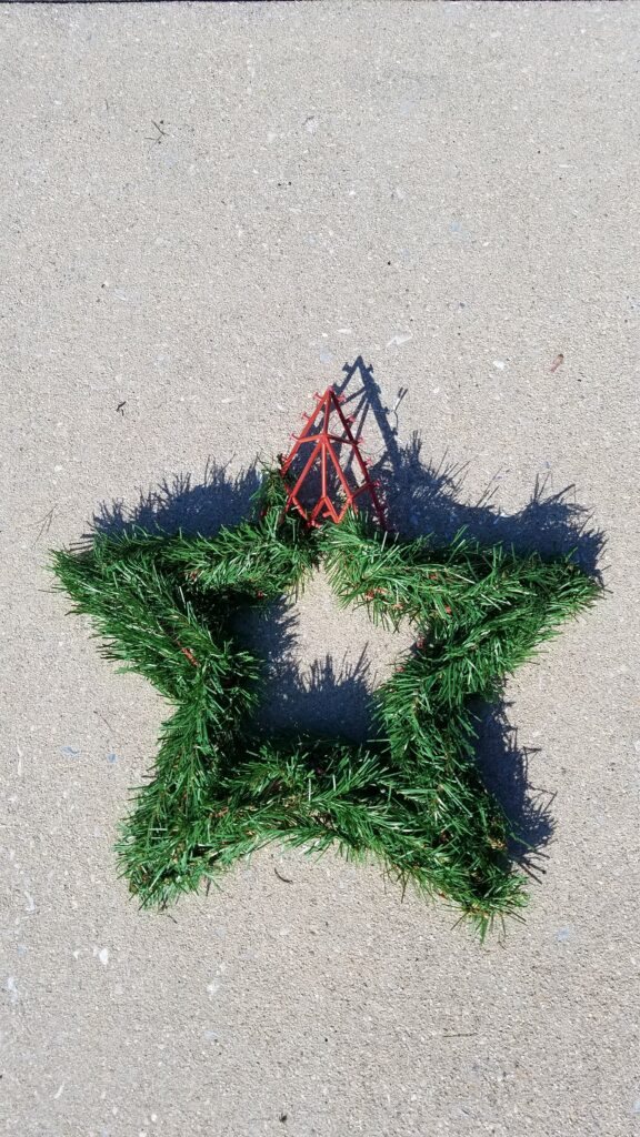 greenery star shaped wreath with one corner exposed showing plastic wreath form