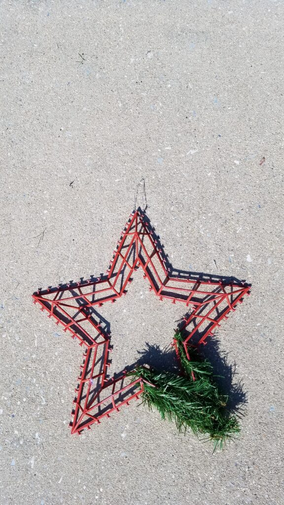 red plastic 5 point star shaped wreath form with some greenery on one corner