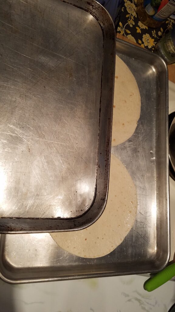 two flour tortillas on a cookie sheet with another cookie sheet partially covering them
