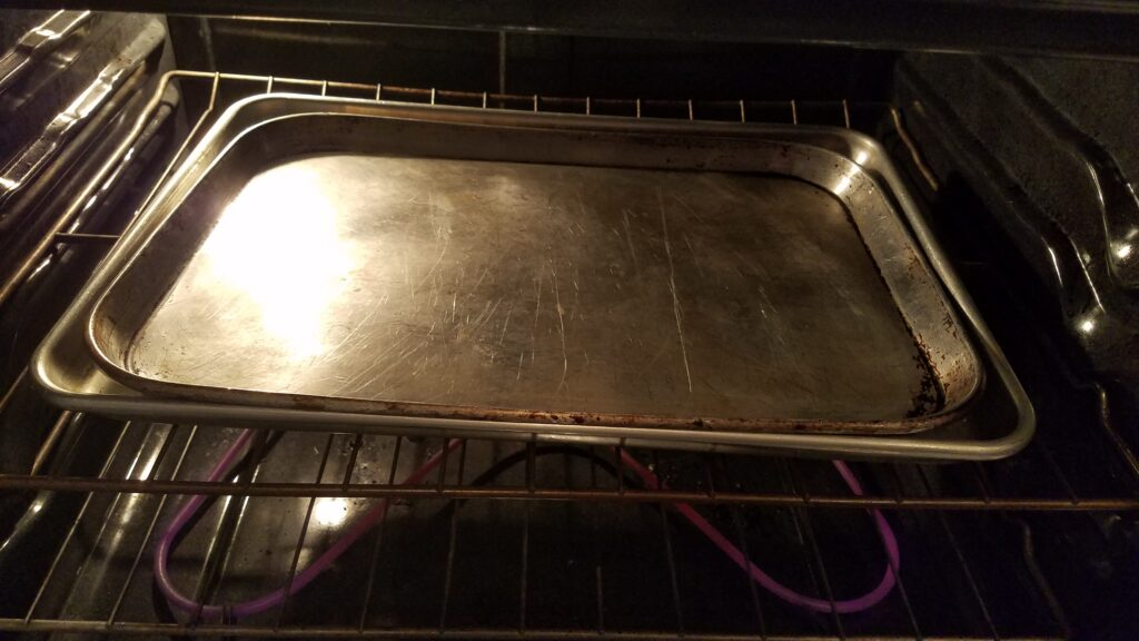 two cookie sheets on top of each other in the oven