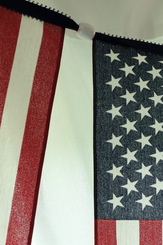 closeup of white wooden bead between flags