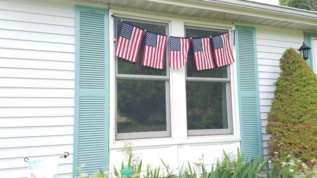 5 flags on banner in front of windows on house with green shutters