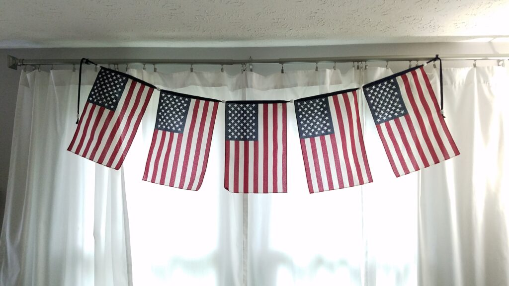flag banner hanging inside house over white curtained windows