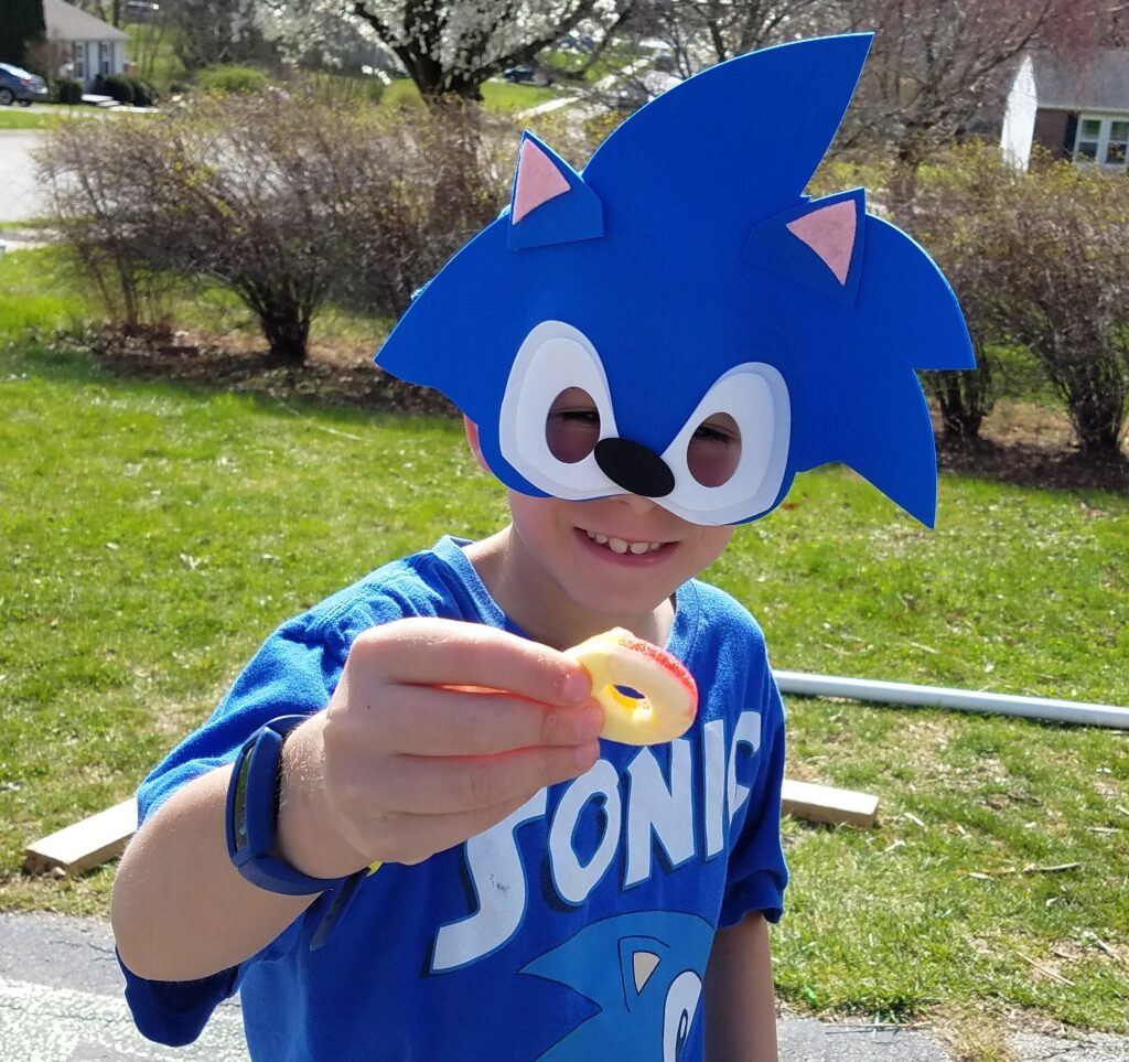 boy wearing a sonic the hedgehog face mask holding a gummy ring