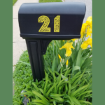 black mailbox with custom yellow numbers on it