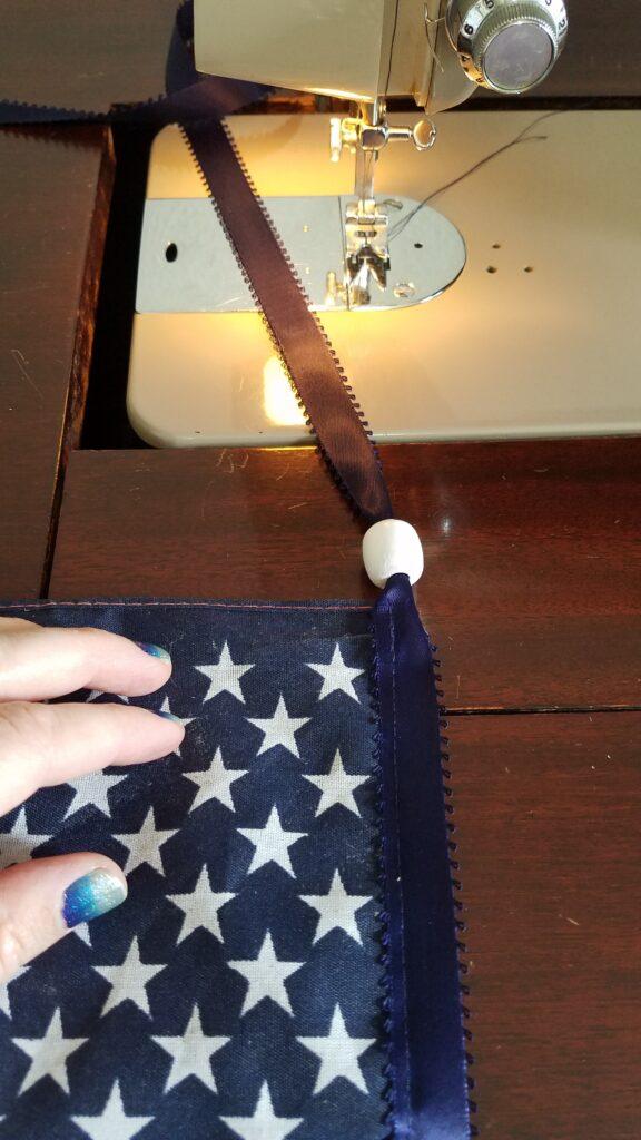 white bead on navy ribbon near sewing machine