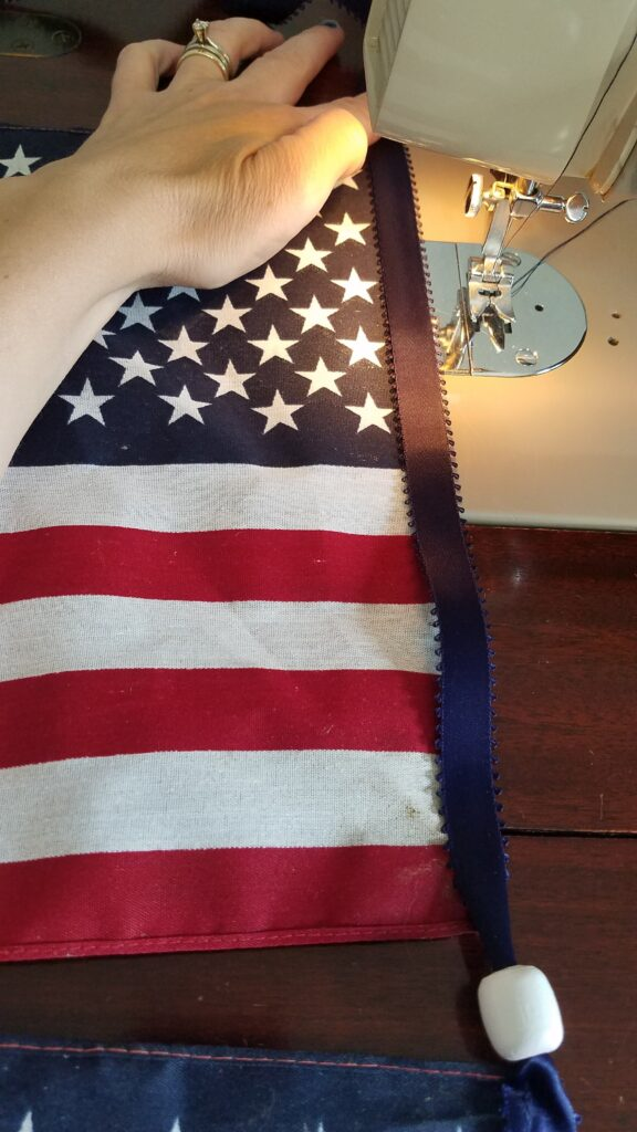 navy ribbon and flag at sewing machine ready to sew