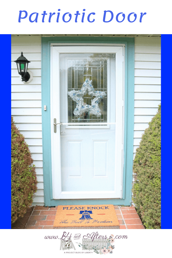 white door with green trim and white star wreath with blue accents and Liberty Bell doormat