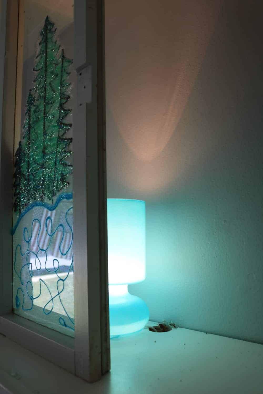 light behind winter window scene that is lighting it up