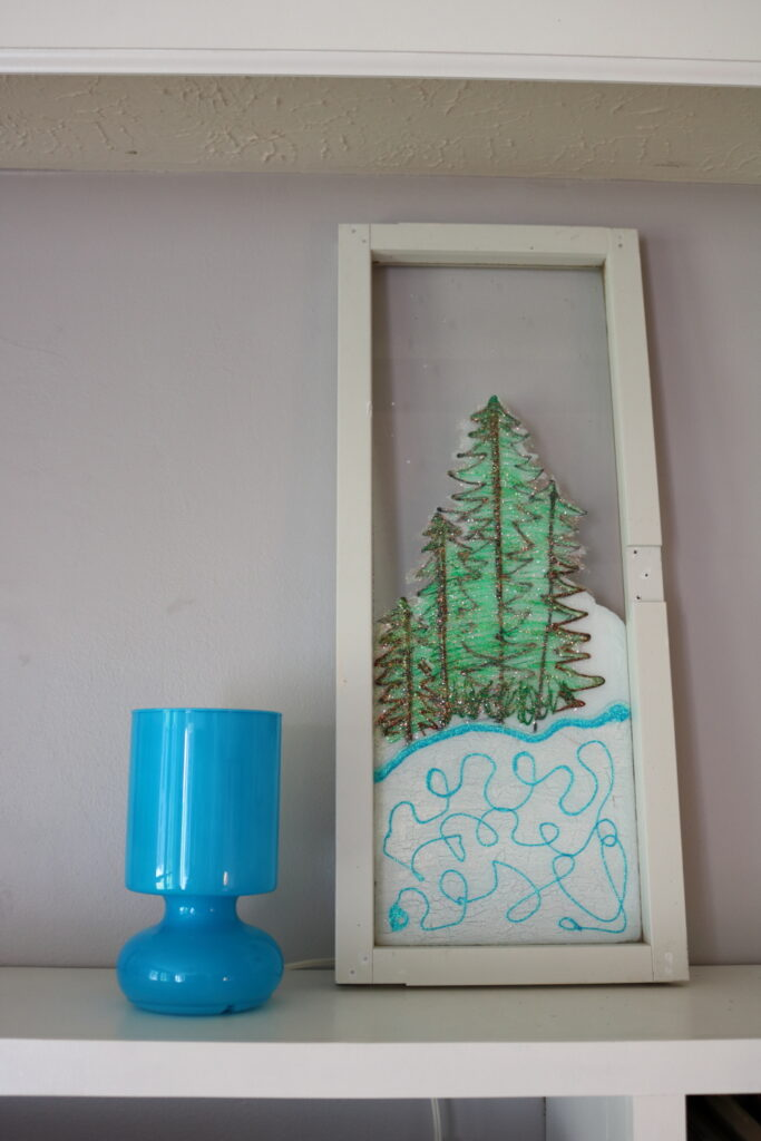 blue lamp next to window winter scene