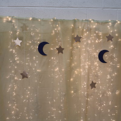 backdrop lit with white Christmas lights, and stars and moons hanging