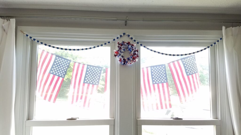 flag banner outside windows with blue and white bead garland and star wreath inside windows