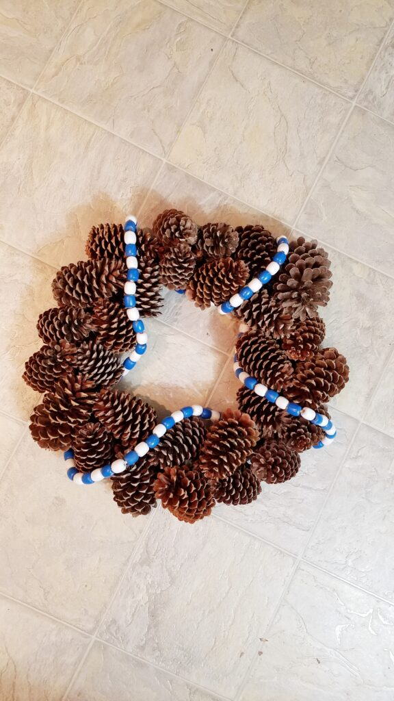 blue and white wood bead garland on pine cone wreath