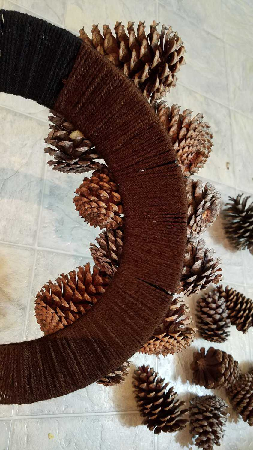 back of yarn wrapped pine cone wreath