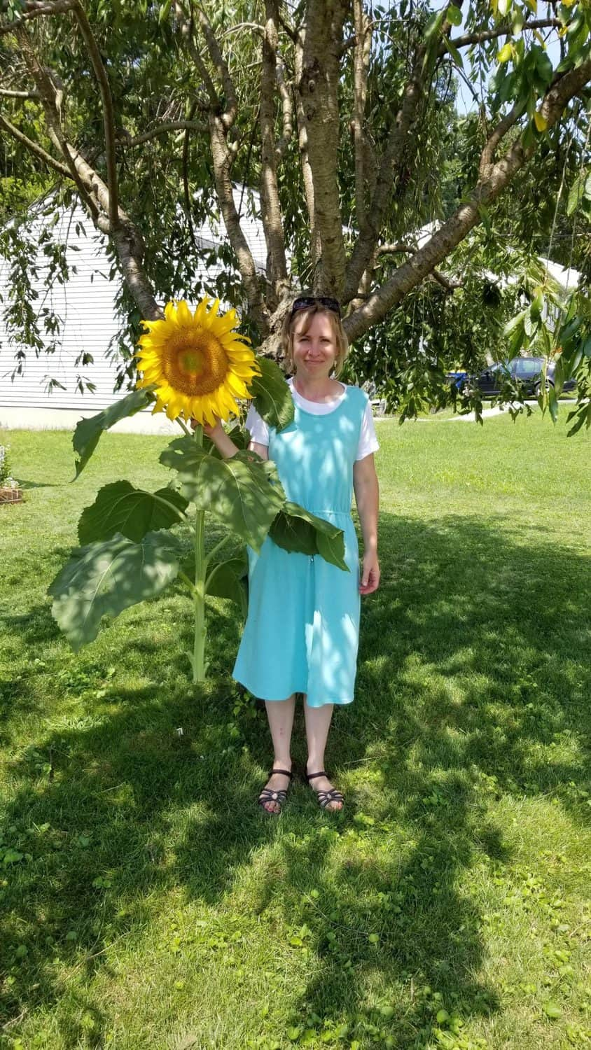 me holding a huge gigantic enormous sunflower that I grew