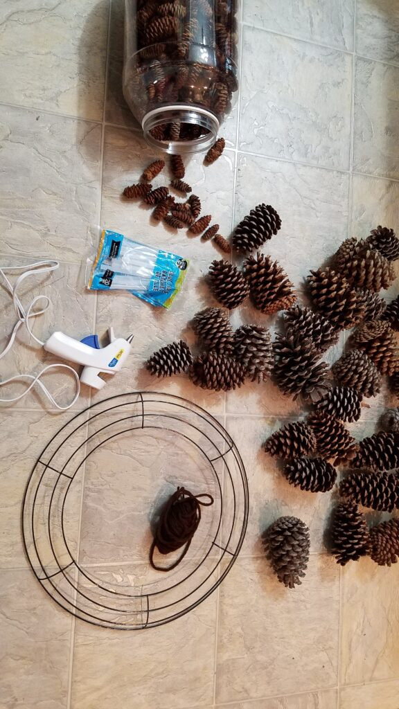Pine cones, glue gun, glue sticks, wire wreath frame