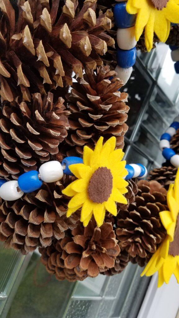 closeup of felt sunflower on pine cone wreath