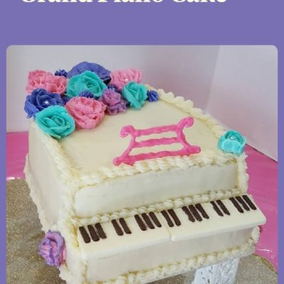 white grand piano cake with pink, purple, and teal flowers