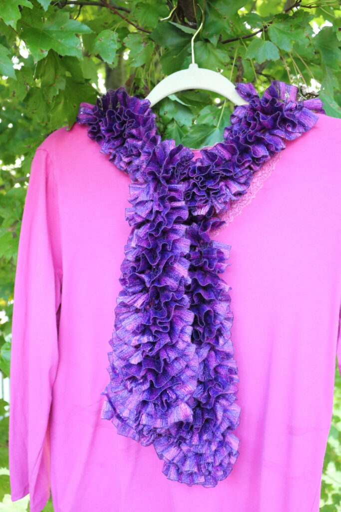 purple and pink scarf tied on a pink shirt