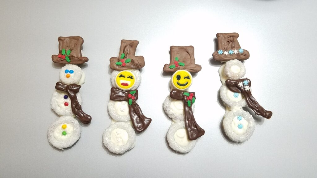 four pretzel snow people with chocolate scarves and hats