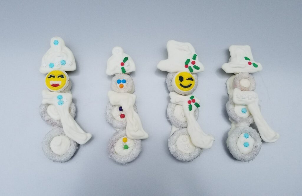 4 white chocolate covered snowmen with scarves and hats and faces
