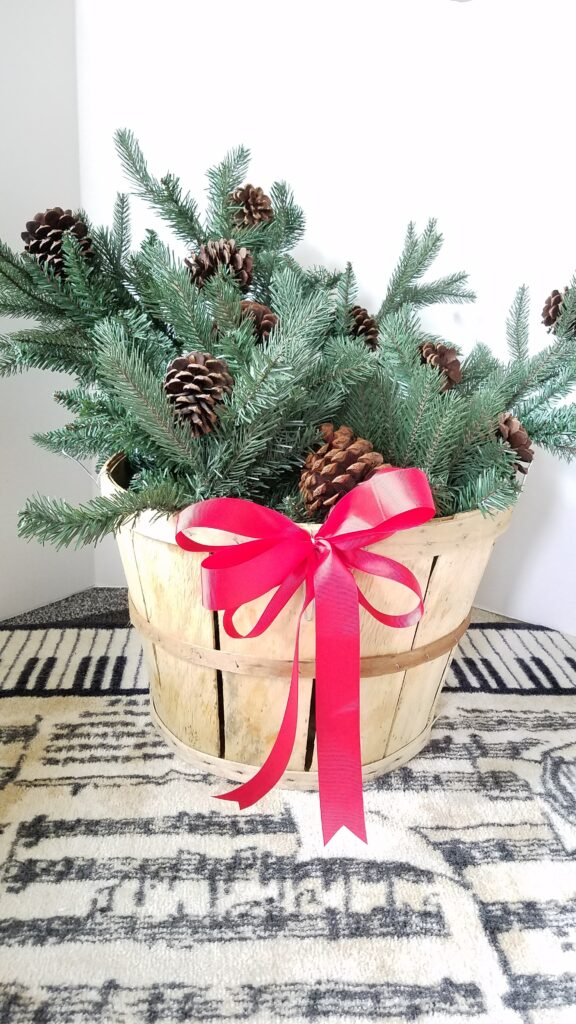 Evergreen Christmas basket with red ribbon and pine cones