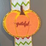 felt pumpkin on a ribbon on a cabinet door