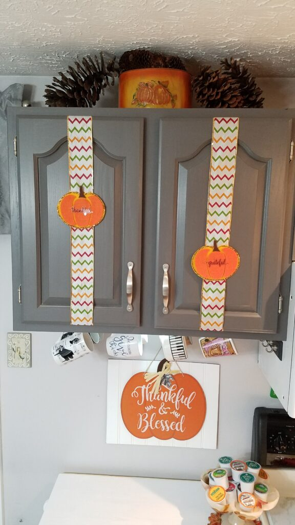 orange felt pumpkins on chevron ribbon on gray cabinet doors