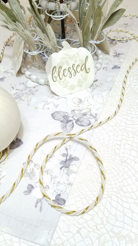 gold and white cord with white pumpkin napkin that says blessed
